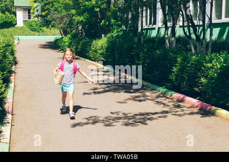 Little girl with a pink backpack and a paper bag with a bite goes to school. School concept. Horizontal frame. - Stock Photo