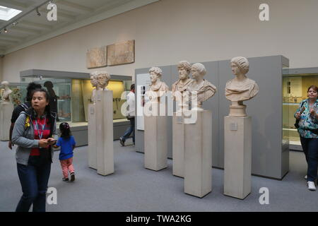 Visitors walk past the collection of ancient marble Roman busts and sculptures on display in the British Museum in London, United Kingdom. - Stock Photo