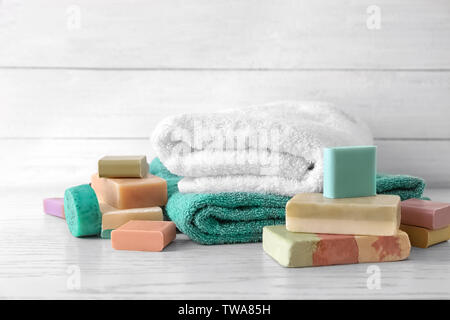Soft towels and different soap bars on table - Stock Photo
