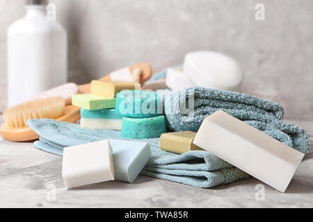 Soft towel and different soap bars on table - Stock Photo