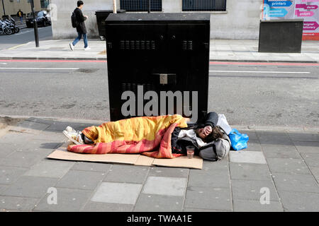 A homeless man sleeping on a pavement, Edgware Road, central London - Stock Photo