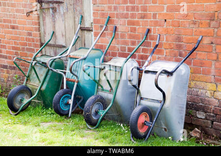 A row of four wheel barrows against an old rustic wall. - Stock Photo