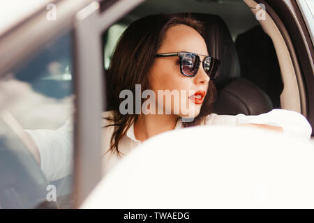 Beautiful successful elegant brunette young woman with red lips in sunglasses driving the passenger car