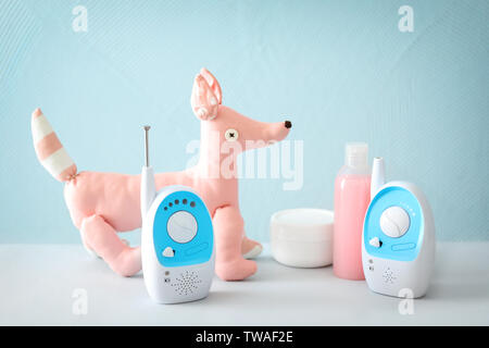 Baby monitors, toys and cosmetics on table against color background - Stock Photo