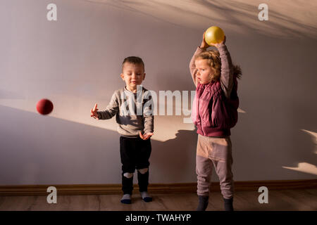 Two children playing inside, in a sunlit room, with little bouncing balls, throwing them up in the air - Stock Photo