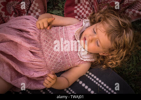 Little beautiful, adorable girl, with curly hair, in cute, pink retro dress, relaxing outside, laying on blankets, on grass - Stock Photo