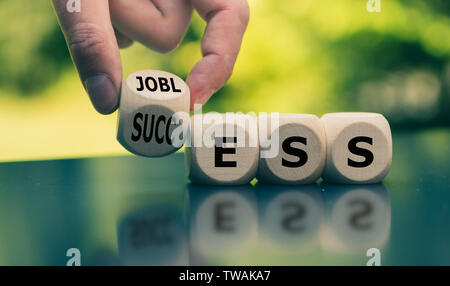 Concept of a turning point in life. Hand turns a cube and changes the word 'jobless' to 'success'. - Stock Photo