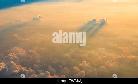 Beautiful aerial view of clouds at sunset, some clouds projecting dramatic shadows. View from airplane. - Stock Photo
