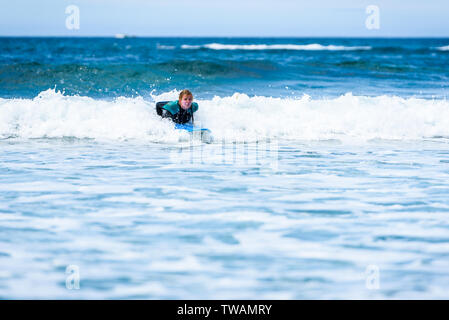 Surfer woman with surfboard is paddling on the wave. Girl in surfing wet suit is paddling the waves of cold atlantic ocean in Galicia, Spain. - Stock Photo