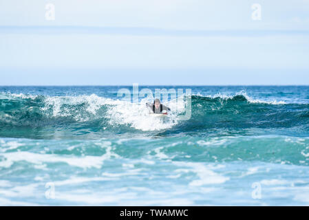 Surfer man with surfboard is paddling on the wave. Guy in surfing wet suit is paddling the waves of cold atlantic ocean in Galicia, Spain. - Stock Photo