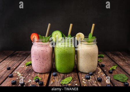 Delicious organic Banana, Strawberry and Cucumber, flax and chia seed fruit smoothies shot on wooden table against a black slate background. Also pict - Stock Photo