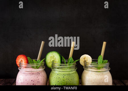 Delicious organic Banana, Strawberry and Cucumber, flax and chia seed fruit smoothies shot against a black slate background. Also pictured are eco Bam - Stock Photo