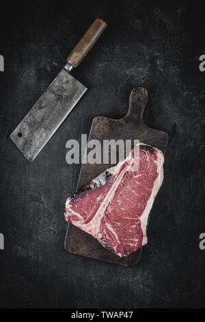 Raw Dry Aged T-bone Steak on Vintage Chopping Board with Meat Cleaver Ready for BBQ - Stock Photo