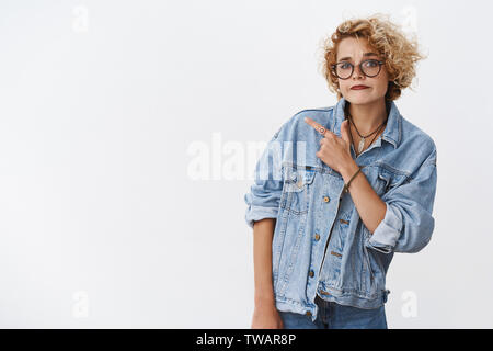 Looks suspicious what you think. Portrait of doubtful unsure and hesitant good-looking stylish girlfriend in denim jacket and glasses pursing chin in - Stock Photo