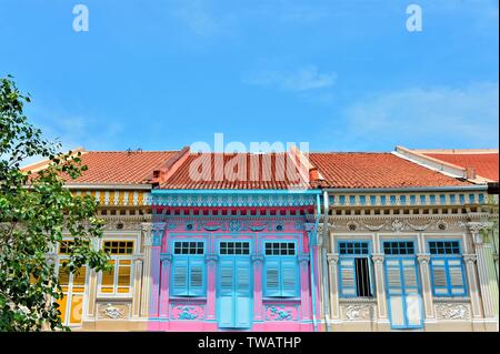 Front view of colourful traditional Singapore Peranakan or Straits Chinese shophouse in historic Joo Chiat East Coast against blue sky