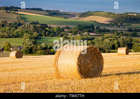 Straw bales on the hill above the villages of Corton and Upton Lovell in the Wylye Valley in Wiltshire. - Stock Photo
