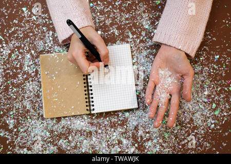 Hands on the table with a pen and notepad. Reflections, doubts about life and plans on the eve of the New Year and Christmas 2018 - Stock Photo