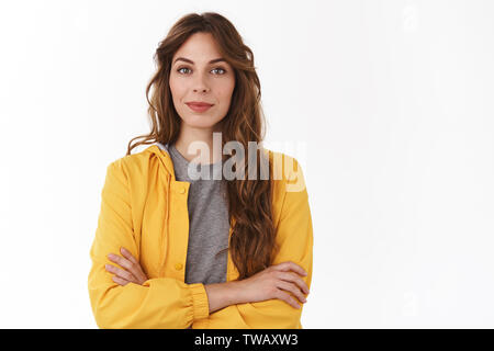 Determined professional successful good-looking young female entrepreneur stylish yellow jacket cross arms chest self-assured smirking delighted - Stock Photo