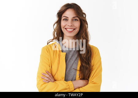 Cheerful young new attractive female employee ready help energized look upbeat confident camera cross arms chest self-assured smiling toothy aim - Stock Photo