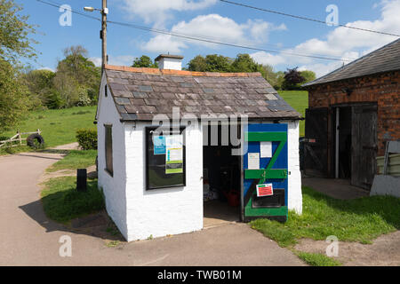 A small, white-painted brick canal lock keeper's hut in bright sunshine. The door is open and there's an information board on the outside wall. - Stock Photo