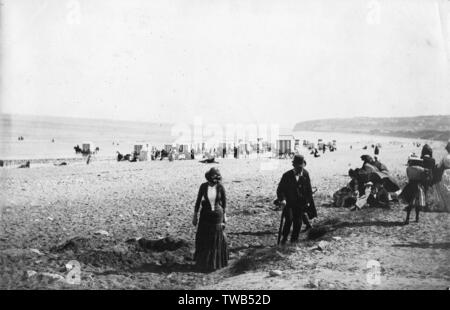 People on the beach at Colwyn Bay, North Wales, with bathing huts in the background.      Date: circa 1889 - Stock Photo