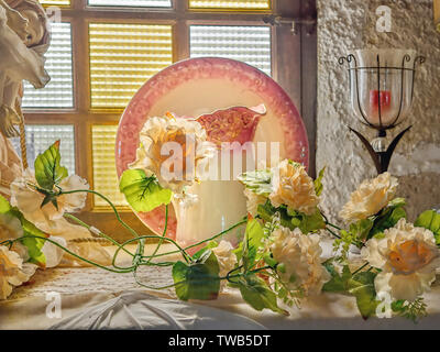 Still life with delicate yellow roses, glass candlesticks, an old upstanding plate with pink flower border, in front of it a matching water carafe in