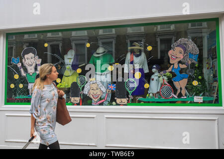 A Pedestrian walks past a shop front in Wimbledon High Street being decorated with tennis themes as Wimbledon prepares to host the 2019 Wimbledon Tennis Championships. - Stock Photo