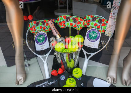 A shop front in Wimbledon High Street   is being decorated with tennis themes as Wimbledon prepares to host the 2019 Wimbledon Tennis Championships. - Stock Photo