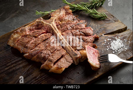 Porterhouse steak is grilled and sliced on a piece of wooden Board. rustic style, top view - Stock Photo