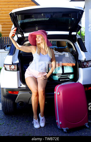 Woman in pink hat loading multicolored suitcases in the trunk of car. Girl makes selfie on a cell phone and ready for travel. - Stock Photo