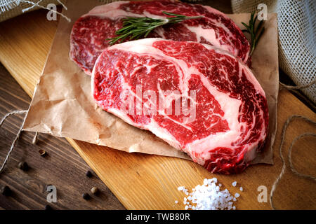 Two raw rib eye steak on a wooden Board on a table prepared for the grill. Top view rustic style - Stock Photo