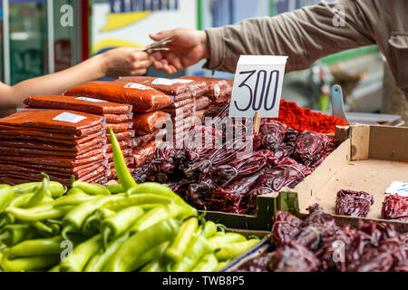 Different types of green and red peppers on the marketplace in Belgrade. Blurred background of seller and customer hands paying cash. - Stock Photo