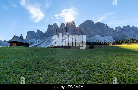Sunburst over the Odle peaks and chapel at Glatschalm, Puez Odle, Dolomites, Funes, Bolzano province, South Tyrol, Italy