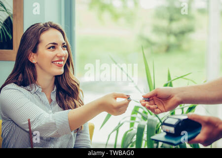 Customer paying for their order with a credit card in a restaurant. Waiter holding a credit card reader machine and returning the debit card to female - Stock Photo