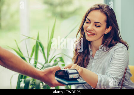 Young woman paying by credit card at cafe. Woman entering security pin in credit card reader with waiter standing at coffee shop. - Stock Photo