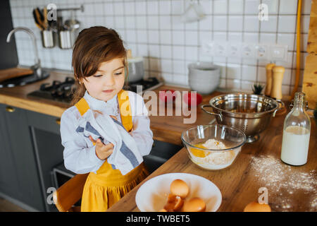 A little cute girl helping mother to bake cookies in the kitchen. Wiping hands with a towel near the bowl with flour. - Stock Photo