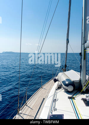 Bow of sailing yacht with land in sight - Stock Photo