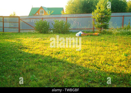 children's toys on the grass in the evening in summer, Russia - Stock Photo