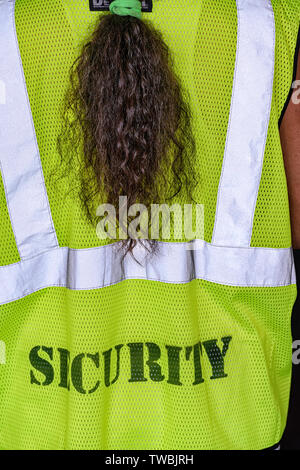 A female security guard with a ponytail,  wearing a high visibility fluorescent yellow-green safety vest - Stock Photo