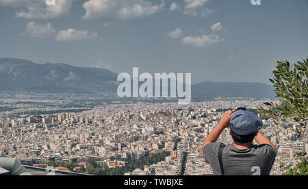man or boy with smart-phone taking photo at the city of Athens from the Mount Lycabettus in a sunny day - Stock Photo