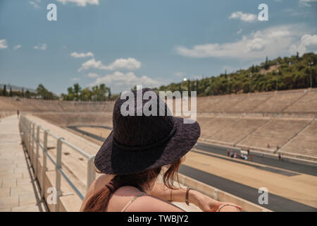 woman or girl with sun hat looking the Panathenaic Stadium from bleachers in a sunny day - Stock Photo