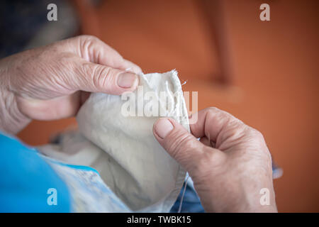 an elderly woman sews torn clothes. close-up of women's hands with thread and needle. the concept of poverty. - Stock Photo