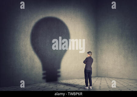 Full length young businesswoman holding hands folded casting a light bulb shape shadow on the wall. Ambition and business idea concept. Motivation and - Stock Photo