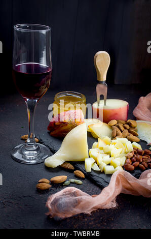 Assorted homemade cheesy Pasta filata, Provolone in various shapes and sizes on the wooden background, suluguni, pigtail, Caciocavallo with tomatoes a - Stock Photo