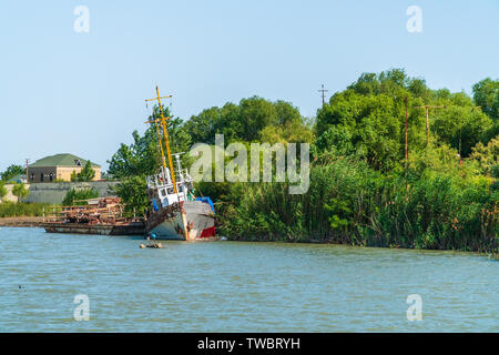 Old abandoned ship on the river bank - Stock Photo