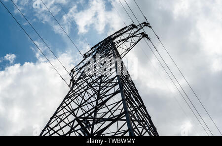 Bottom view of a high-voltage electricity pylon against blue sky with clouds at sunny day. High-voltage power transmission tower. Power engineering. - Stock Photo