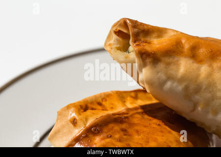 Spanakopita in the shape of a triangle on a plate - Stock Photo