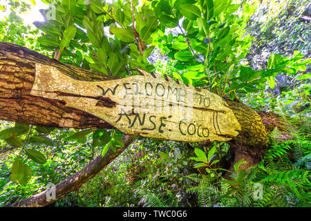 Welcome to Anse Coco sign in tropical jungle. Anse Cocos in La Digue Island, Seychelles is a popular beautiful beach can be reached with a trek - Stock Photo