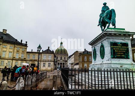 A walking tour group visit Amalienborg Palace, the royal residence in Copenhagen, Denmark. January 2019. - Stock Photo