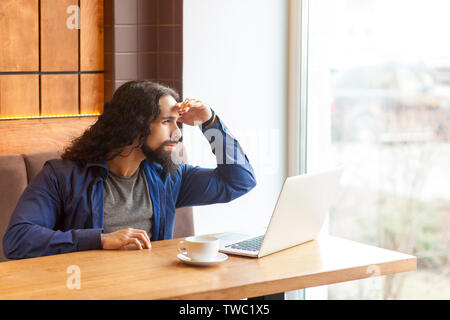 Portrait of serious handsome young adult man freelancer in casual style sitting in cafe with laptop, waiting someone and looking out the window, bussi - Stock Photo
